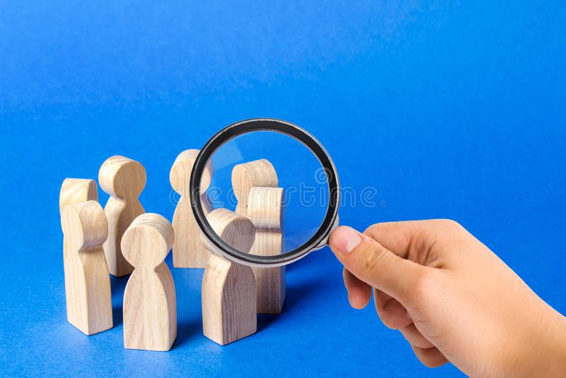 Eine Lupe betrachtet ein Volk, das in einem Kreis steht Diskussion, Zusammenarbeit Arbeitssitzung stockfotos