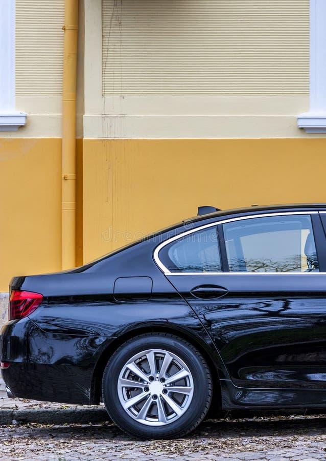 Eine Luxusluxuslimousine geparkt auf der Straße zu einem Haus in der Mitte einer Kleinstadt in Europa lizenzfreie stockfotografie