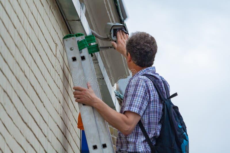 Eine männliche Arbeitskraft erledigt Wartungsarbeiten, indem er eine Sicherheitsüberwachung im Freien kontrolliert und säubert lizenzfreie stockfotografie