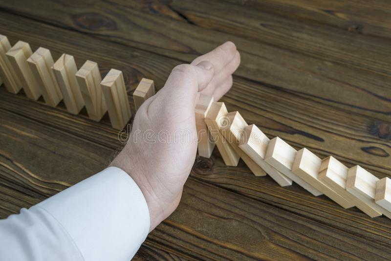 Eine männliche Hand, die den Domino-Effekt stoppt stockbild