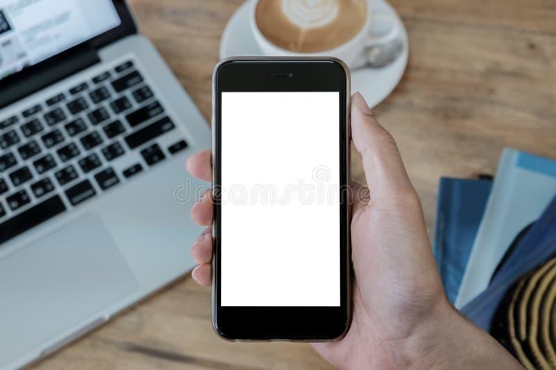 Eine männliche Hand mit Smartphone mit Laptop und Ohrhörer auf dem Holzschreibtisch im Coffee Shop Handy mit leerem Bildschirm un stockfoto