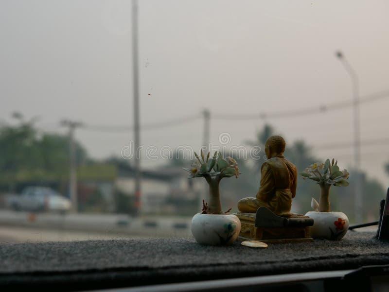 Eine Mönchstatue, die auf ein treibendes Armaturenbrett als das Thais gesetzt wird, glauben, dass die Statue sie vom Verkehrsunfa stockfoto