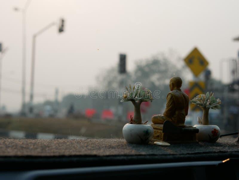 Eine Mönchstatue, die auf ein treibendes Armaturenbrett als das Thais gesetzt wird, glauben, dass die Statue sie vom Verkehrsunfa stockbild