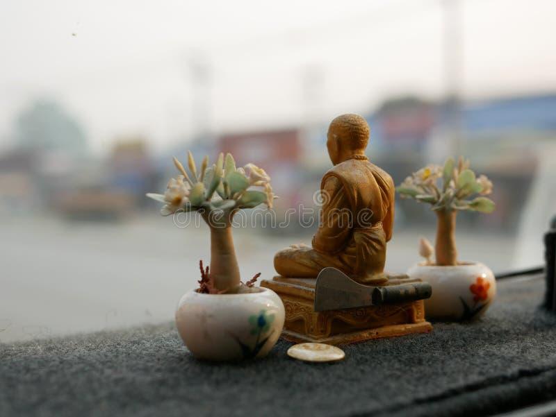 Eine Mönchstatue, die auf ein treibendes Armaturenbrett in Thailand gelegt wird, da der Thais glauben, dass die Statue sie von de stockbild