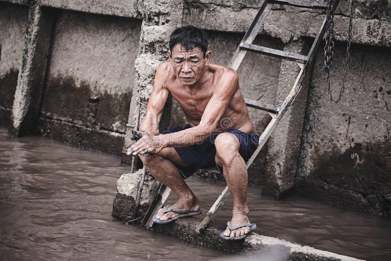 Eine müde asiatische Arbeitskraft wäscht seine Hände im Fluss stockfoto