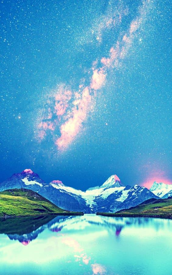 Eine magische Panoramalandschaft mit einem See in den Bergen in den Schweizer Alpen vor dem hintergrund der Sterne und der Milchs lizenzfreies stockfoto