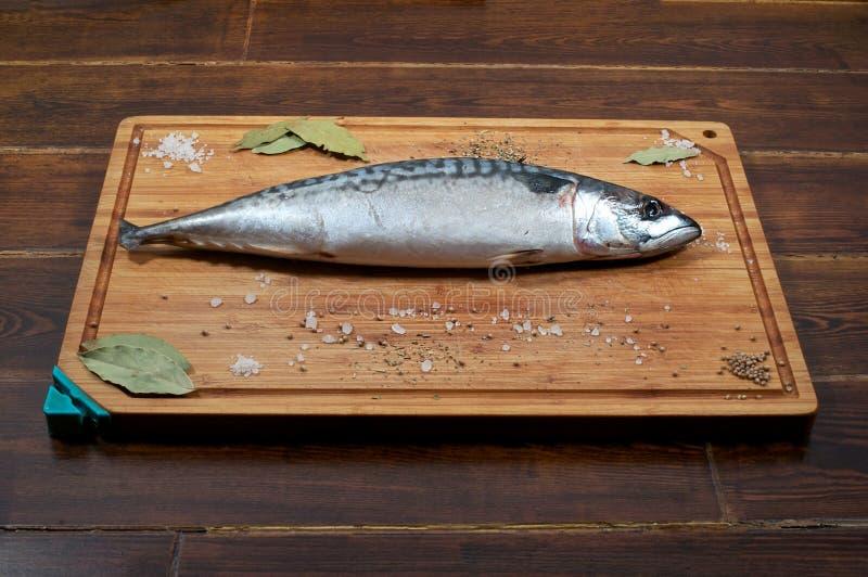 Eine Makrele auf hölzerner Platte mit Gewürzen stockbilder