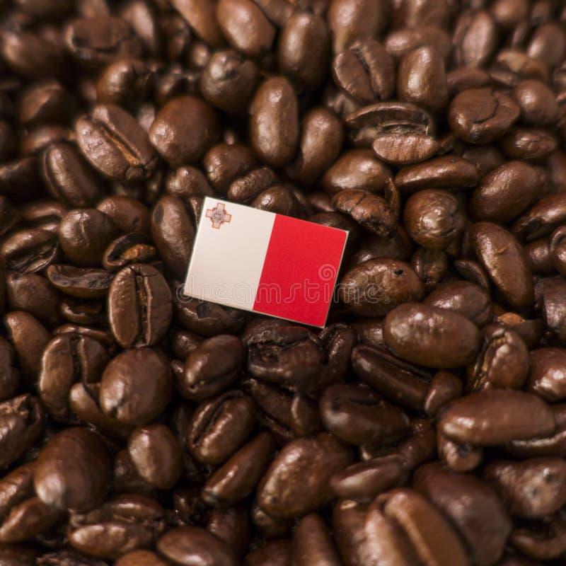 Eine Malta-Flagge gesetzt über Röstkaffeebohnen lizenzfreie stockfotos
