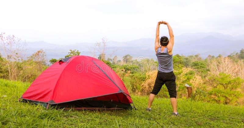 Eine Mannübung und ein Athlet Warming Up am Morgen nahe Zelt auf Camping-Ausflug auf dem Berg stockfotografie