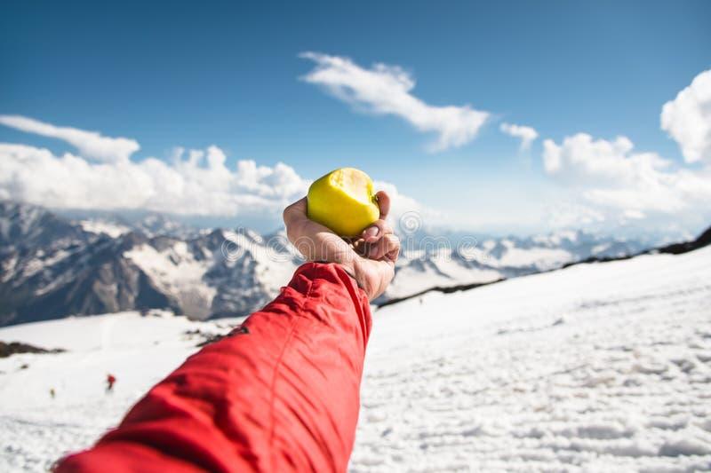 Eine Mann ` s Hand hält einen Apfel mit einem Biss auf dem Hintergrund von schneebedeckten Bergen und von Schnee am Boden stockfotografie