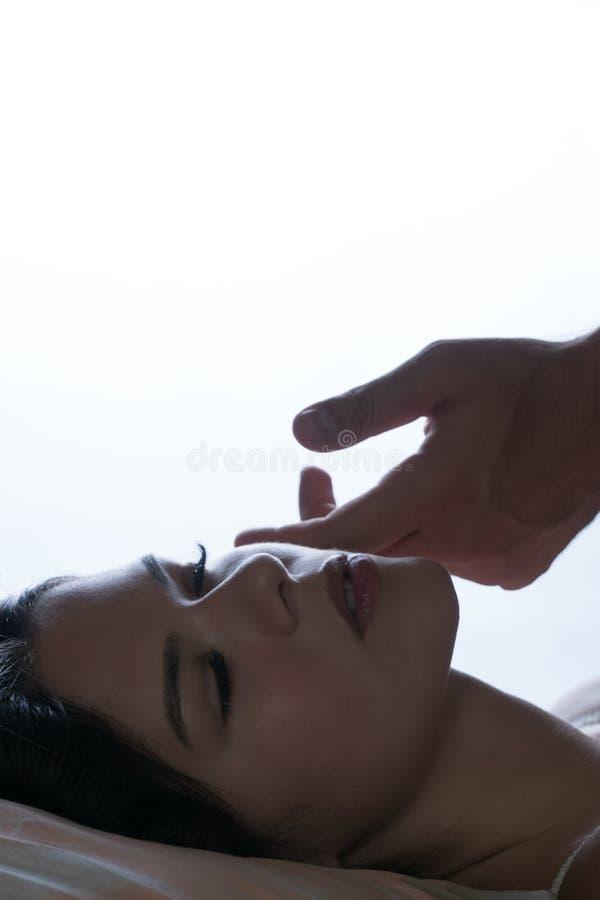 Eine Mann ` s Hand streichelt das Mädchen ` s Gesicht morgens Morgen weckend Zurück von einem unscharfen weißen Hintergrund lizenzfreies stockbild