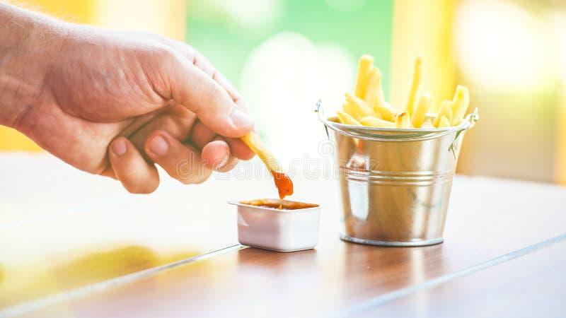 Eine Mann ` s Hand taucht Kartoffeln in eine apetitou Soße, Pommes-Frites in einem dekorativen Eimer auf einem Holztisch ein lizenzfreie stockfotos