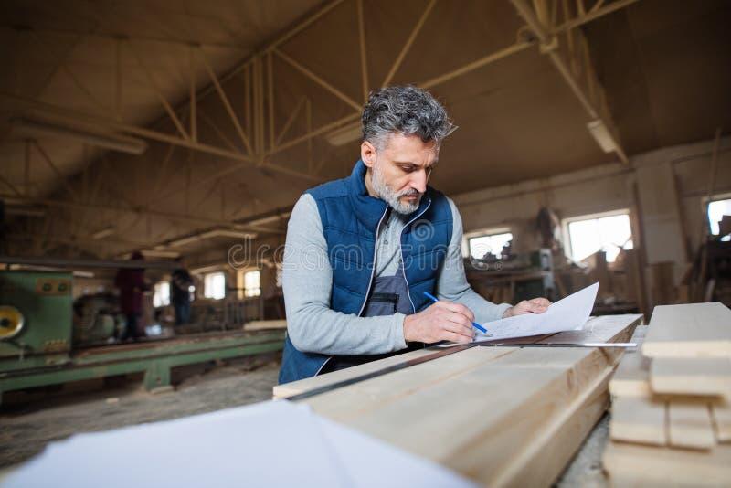 Eine Mannarbeitskraft in der Zimmereiwerkstatt, machend plant stockbild