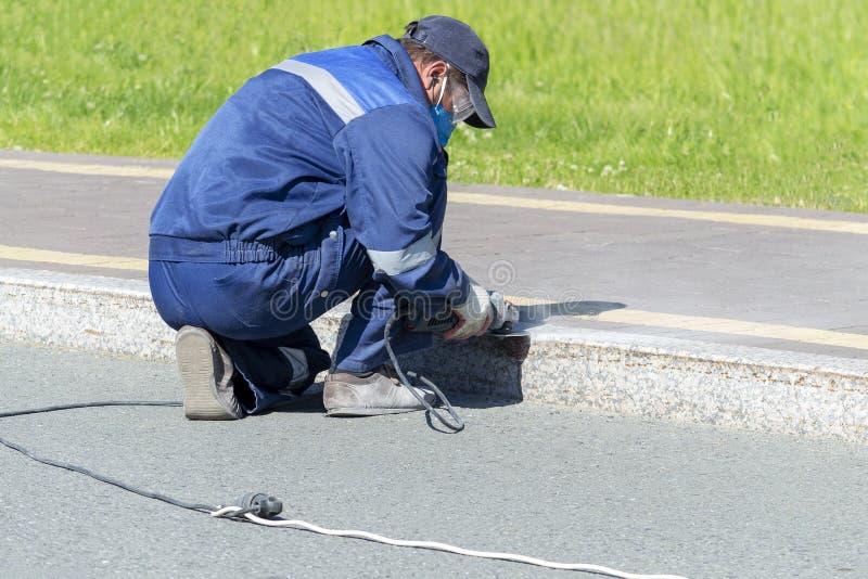 Eine Mannarbeitskraft säubert eine elektrische Marmorierungbeschränkung mit einem elektrischen Handschleifer lizenzfreie stockfotografie