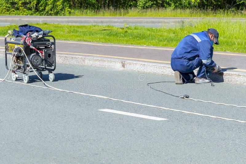 Eine Mannarbeitskraft säubert eine elektrische Marmorierungbeschränkung mit einem elektrischen Handschleifer stockbilder