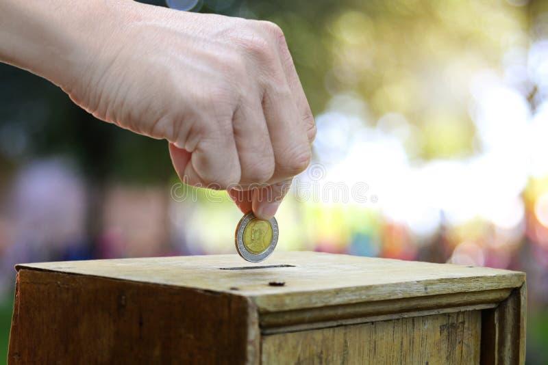 Eine Mannhand, die Münze in eine Holzkiste als Spende setzt lizenzfreie stockbilder