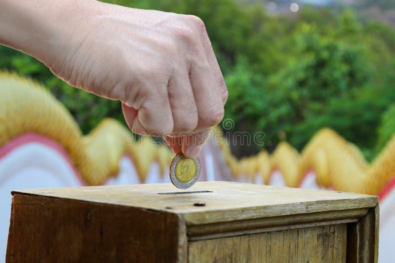 Eine Mannhand, die Münze in eine Holzkiste als Spende setzt lizenzfreies stockbild