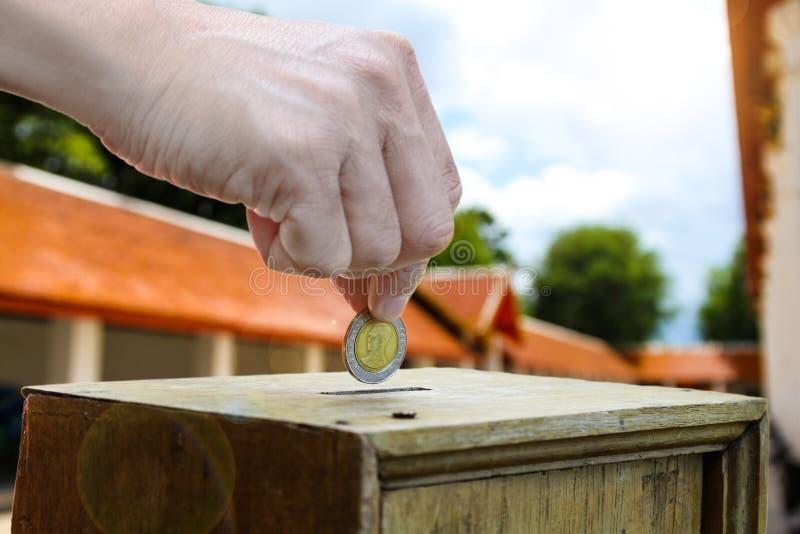 Eine Mannhand, die Münze in eine Holzkiste als Spende setzt stockfotografie