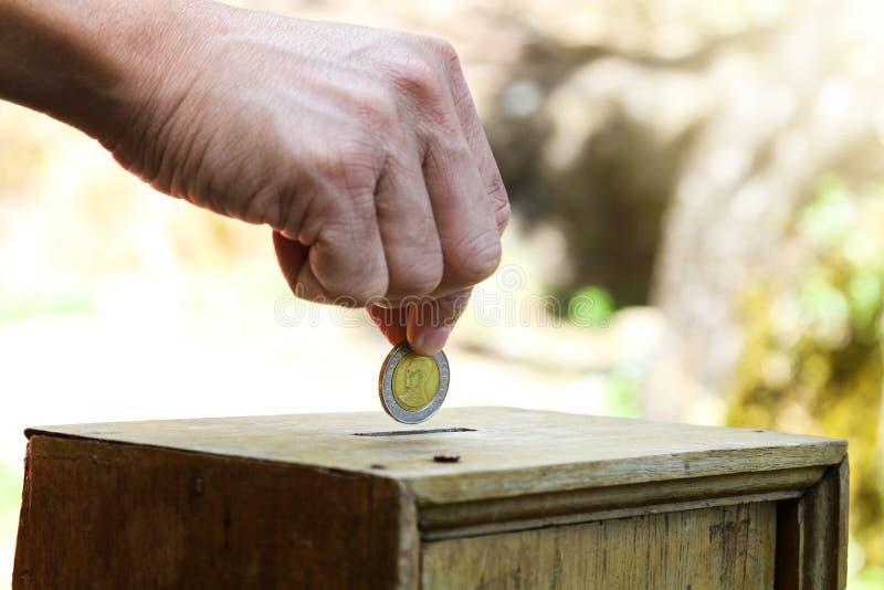 Eine Mannhand, die Münze in eine Holzkiste als Spende setzt stockbilder