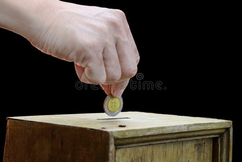 Eine Mannhand, die Münze in eine Holzkiste als Spende setzt stockfoto
