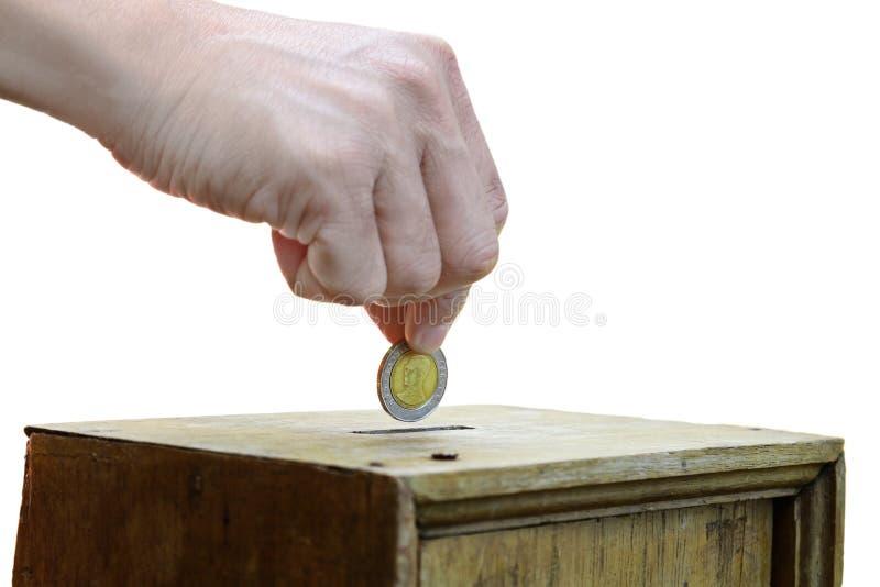 Eine Mannhand, die Münze in eine Holzkiste als Spende setzt lizenzfreie stockfotografie