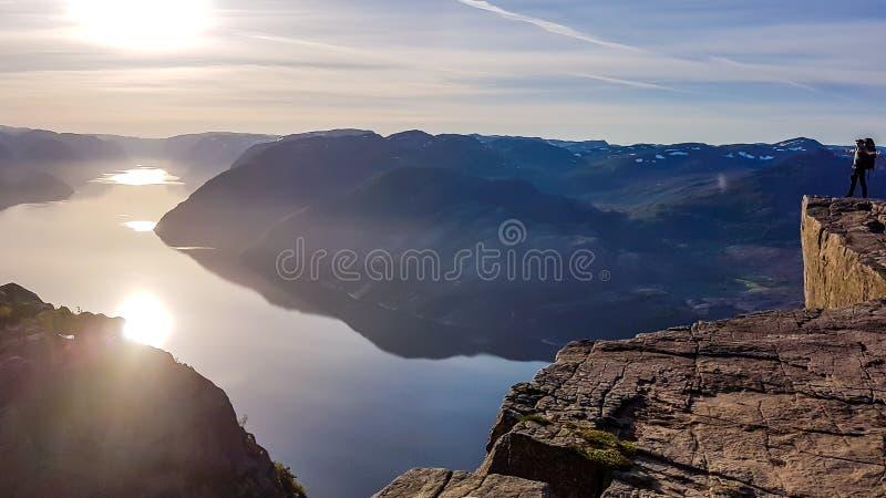Eine Mannstellung auf ber?hmtem Preikestolen-Felsen in Norwegen Der Sonnenaufgang findet über dem Fjord statt lizenzfreie stockbilder