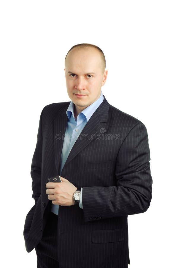Eine Mannstellung und -holding ein Mobile in seiner Hand lizenzfreie stockbilder