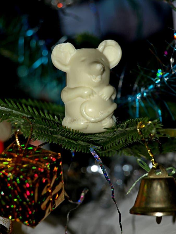 Eine Maus auf einem Weihnachtsbaum - mit einem Geschenk und einer Glocke stockbilder