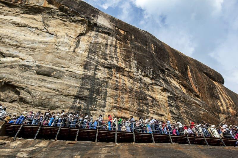 Eine Menge von den Leuten, die in Richtung zum frescoe umziehen, höhlen auf Sigiriya-Felsen in zentralem Sri Lanka aus lizenzfreie stockfotografie