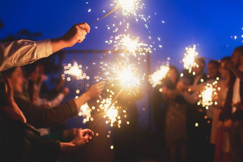 Eine Menge von jungen glücklichen Menschen mit Bengal-Feuerwunderkerzen in ihren Händen während der Geburtstagsfeier lizenzfreie stockfotografie