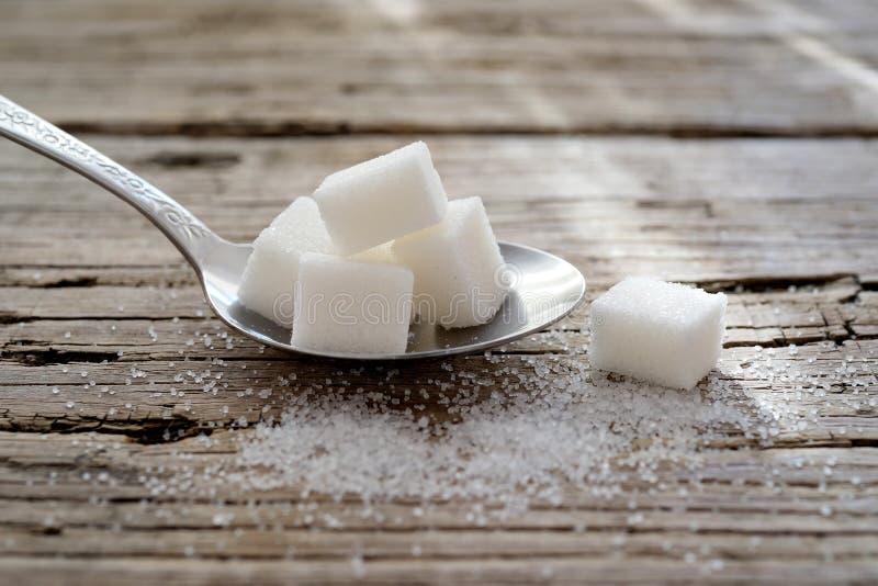 Eine Metallschaufel des Zuckers und des Würfelzuckers lizenzfreie stockbilder