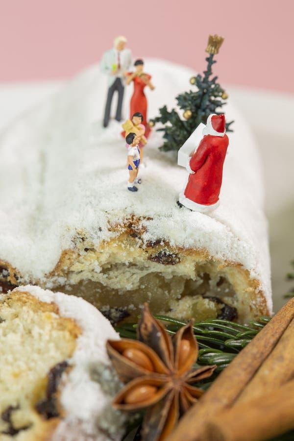 Eine Miniaturfamilie feiert Weihnachten auf einem Weihnachtsstollen mit einer kleinen Weihnachtsbaum- und Santa-Klausel stockbilder