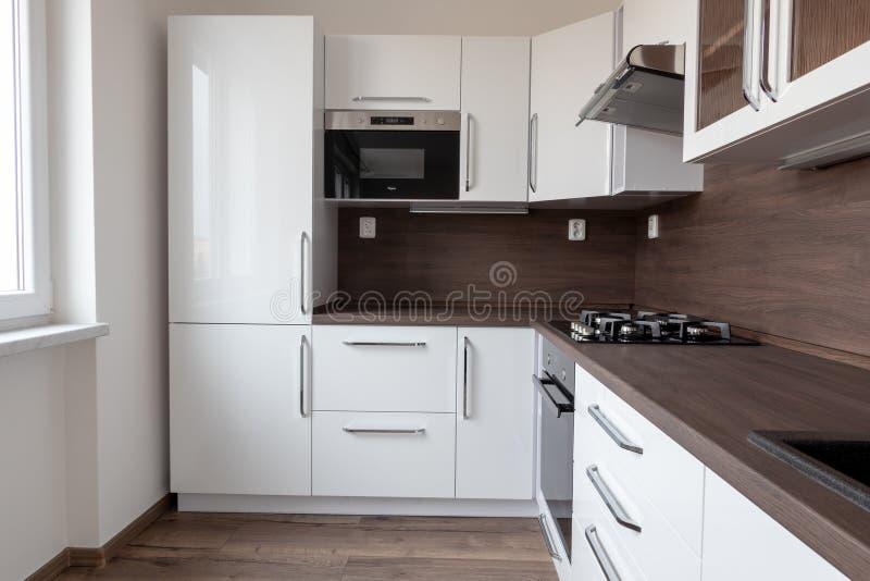 Eine moderne Küche in L-Form mit dunkelbraunem Schreibtisch, weißen Farbtönen und integriertem Kühlschrank. stockfotografie