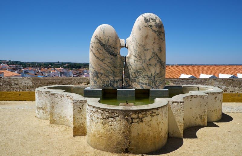 Eine moderne Straßenkunst-Marmorskulptur von den Paaren, die nahe Brunnen am Ausblickpunkt des Gartens von Diana sitzen Evora por lizenzfreie stockfotografie