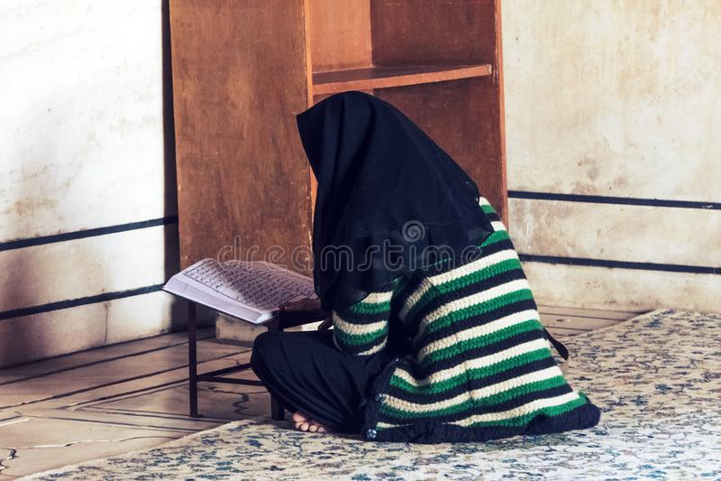Eine moslemische Frau mit einem schwarzen Kopftuch stockfotos