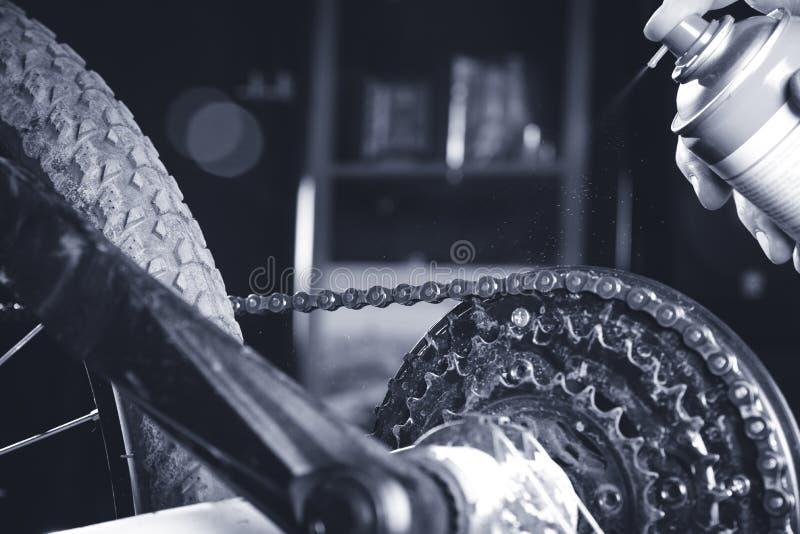 Eine Motorradkette und -gang mit Öl Spray/dunklem Licht säubern und ölend stockbild
