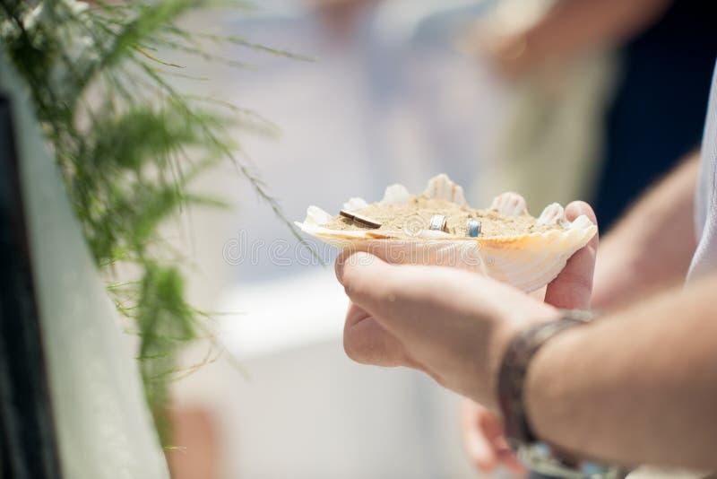 Eine Muschel, die mit Sand gefüllt wird, ist die Basis für zwei Eheringe ist lizenzfreies stockbild