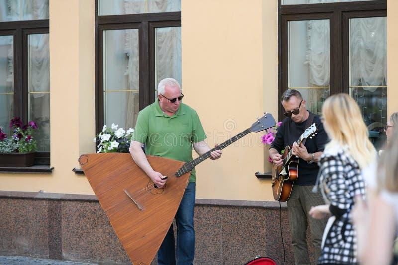 Eine musikalische Gruppe von drei Leuten auf einer alten europ?ischen Stra?e Das Band besteht zwei M?nnern und aus einem M?dchen  lizenzfreie stockbilder