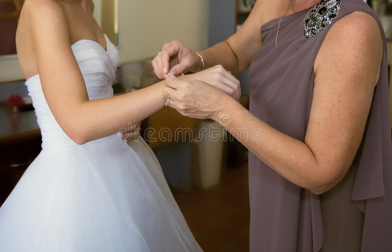 Eine Mutter befestigt ein Armband an ihrem Tochter ` s Handgelenk vor ihrer Hochzeit lizenzfreie stockfotos