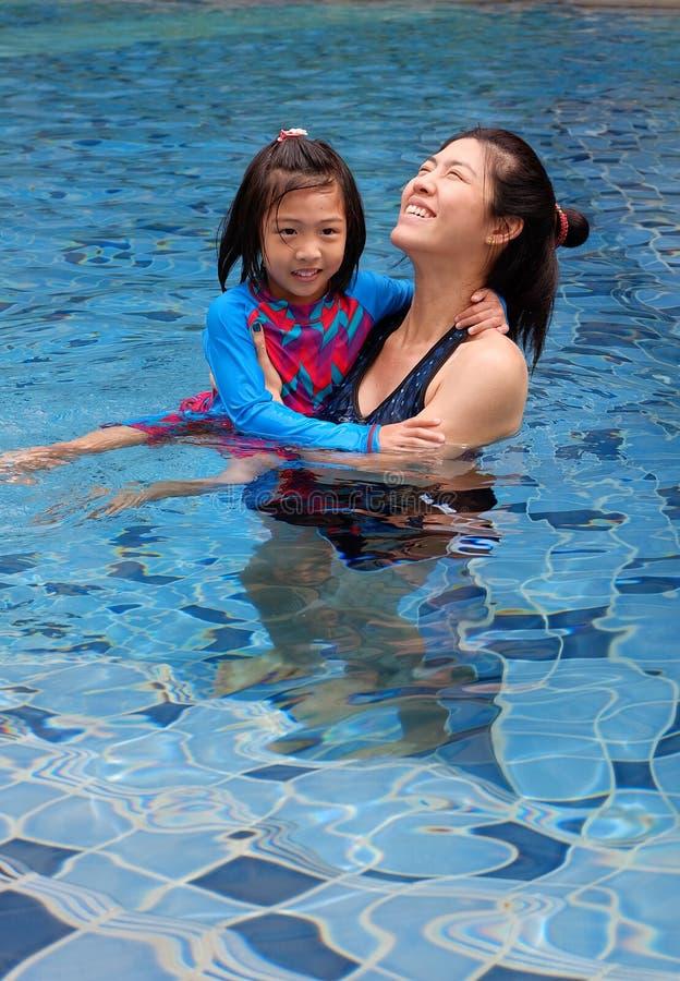 Eine Mutter, die ihre Tochter unterrichtet zu schwimmen stockfotografie