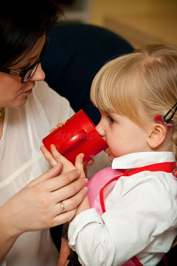 Mutter mit Tochtergetränk vom Becher stockbilder