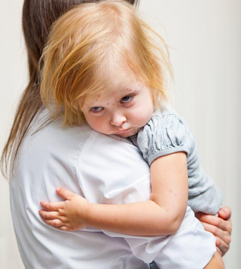 Eine Mutter hält ein krankes Mädchen an. stockbilder