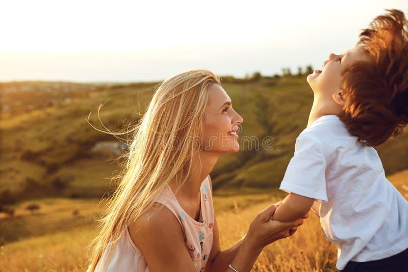 Eine Mutter küsst ihren Sohn in der Natur lizenzfreie stockfotos