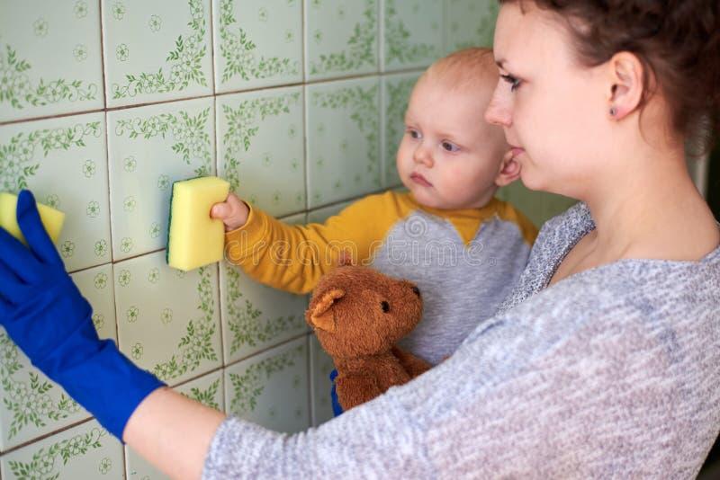 Eine Mutter mit ihrem kleinen Sohn säubert das Haus Das Konzept der Kombination von Hausarbeit und des Aufwachsen eines Kindes lizenzfreie stockbilder