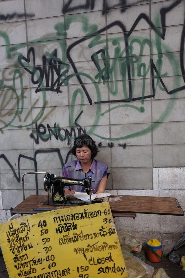 Eine Näherin, die an dem Bürgersteig vor einer Wand bedeckt mit Graffiti in einer Straße von Bangkok arbeitet stockfoto