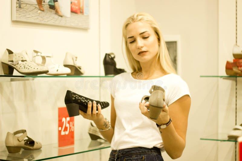 Eine nachdenkliche Frau auf dem Einkaufen wählt Schuhe lizenzfreies stockbild