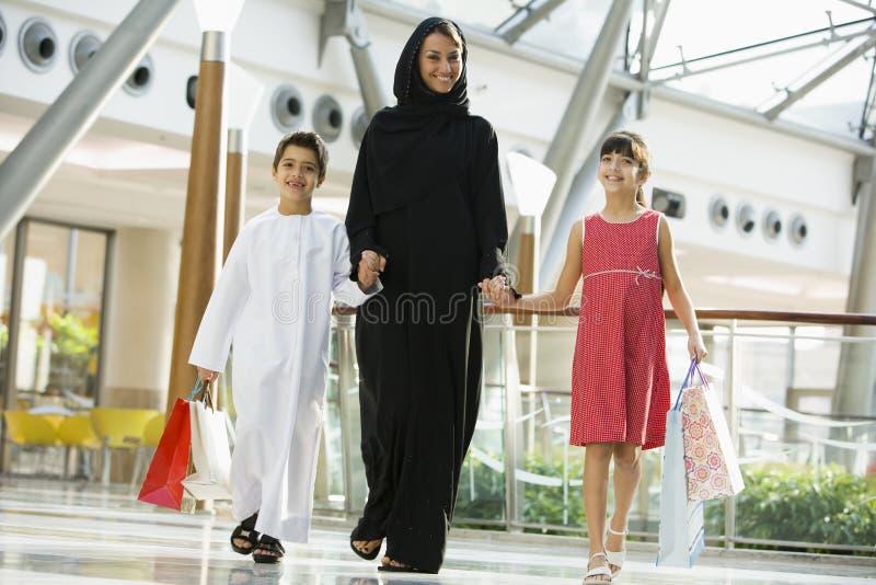 Eine nahöstliche Frau mit dem Einkauf mit zwei Kindern lizenzfreie stockfotos