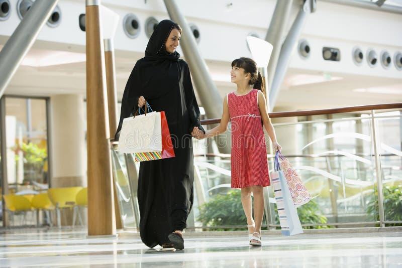 Eine nahöstliche Frau mit einem Mädcheneinkaufen stockbild
