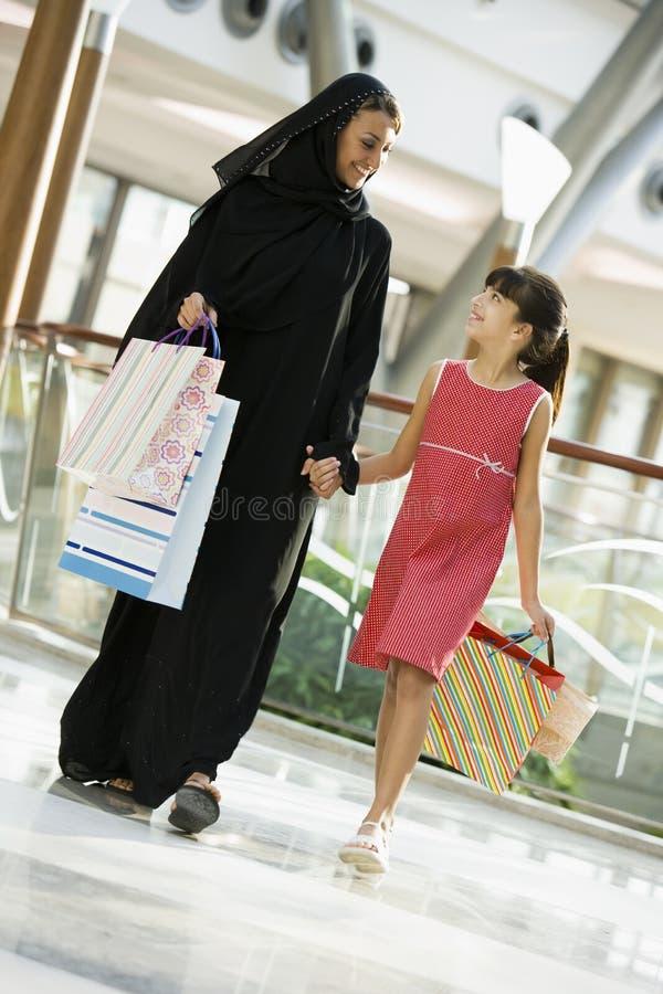 Eine nahöstliche Frau mit einem Mädcheneinkaufen stockfotos