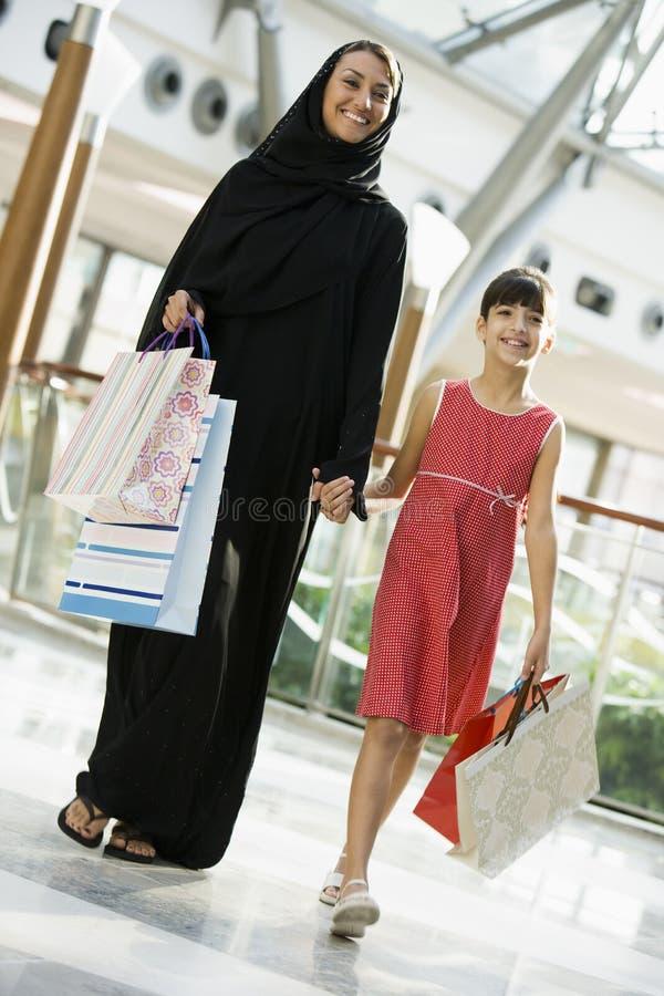 Eine nahöstliche Frau mit einem Mädcheneinkaufen lizenzfreies stockbild